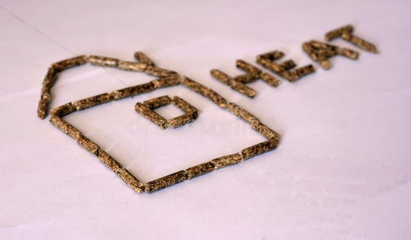 关闭形成房子和信件的形状木药丸燃料五谷仁的图象 库存照片