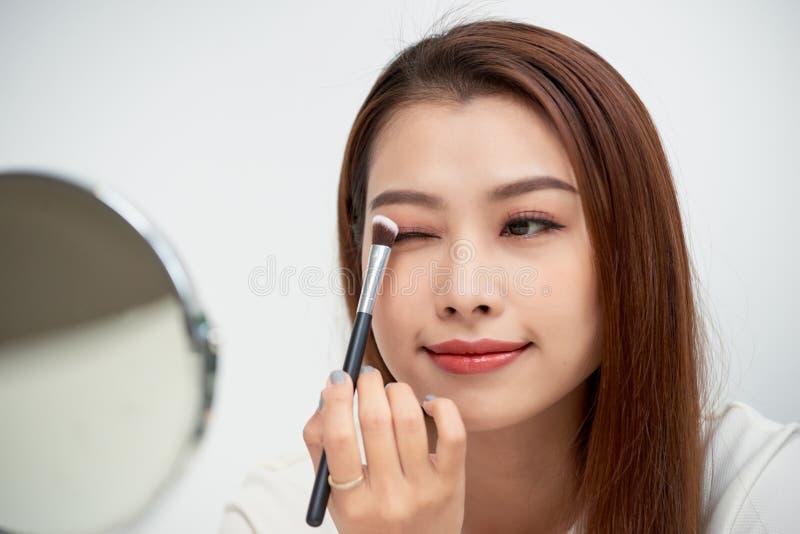 关闭得到构成的亚裔少妇的美丽的面孔 亚裔妇女应用在她的眼眉的眼影膏有刷子的 免版税库存照片