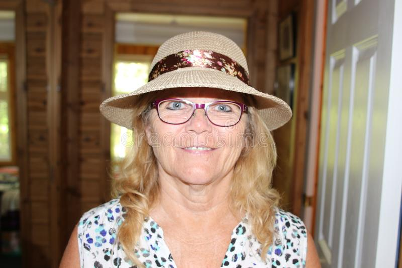 关闭微笑与帽子的一名美丽的更老的资深妇女的画象 库存图片