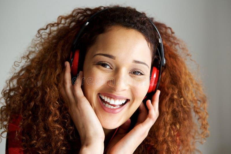 关闭微笑和听到与耳机的音乐的愉快的年轻非裔美国人的妇女 免版税库存图片