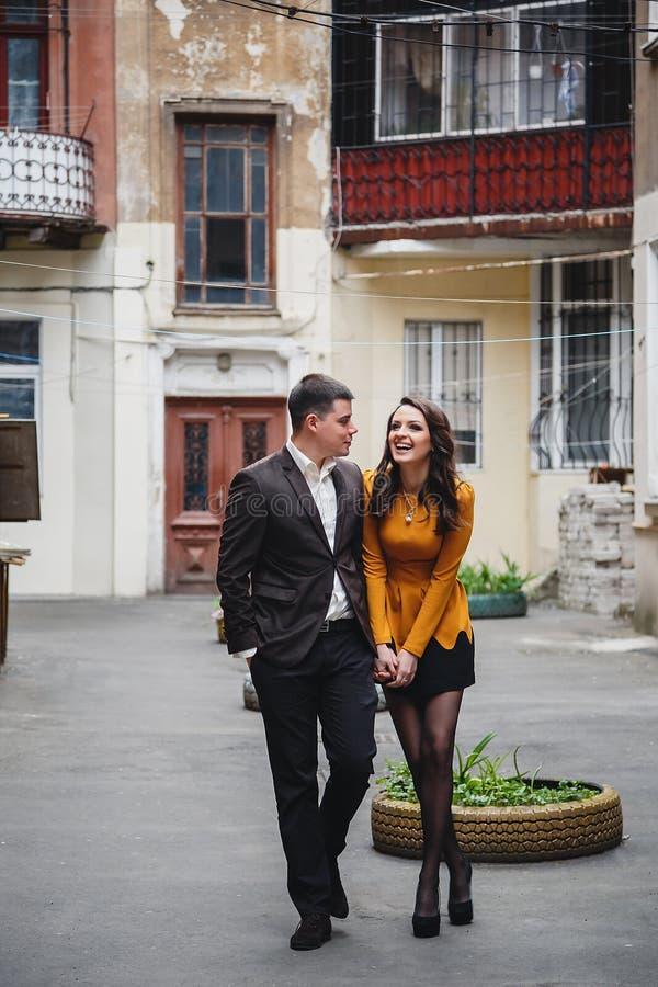 关闭微笑和拥抱在小街道,老城市的愉快的浪漫有吸引力的年轻夫妇 免版税库存图片