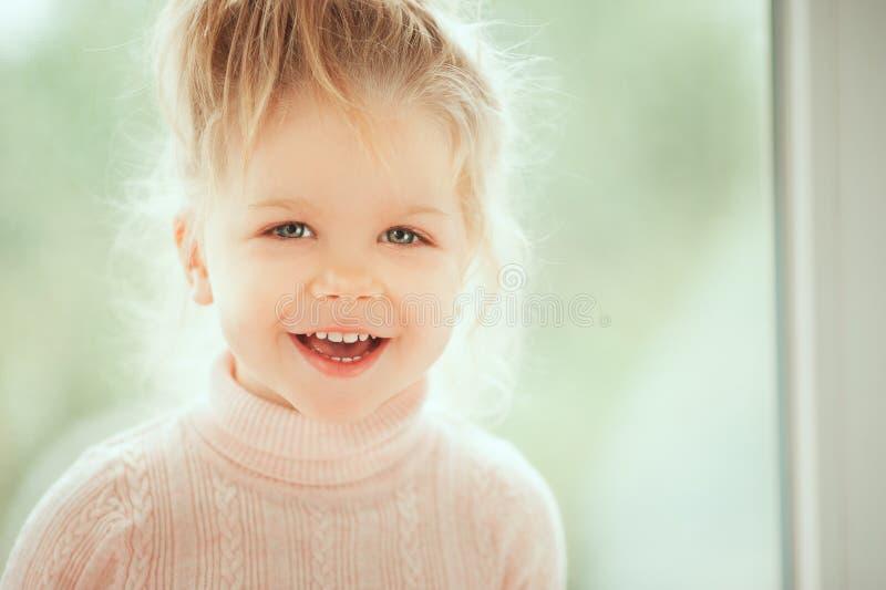关闭微笑和看对凸轮的可爱的美丽的女婴画象  童年哄骗人概念 白种人时尚是 库存照片