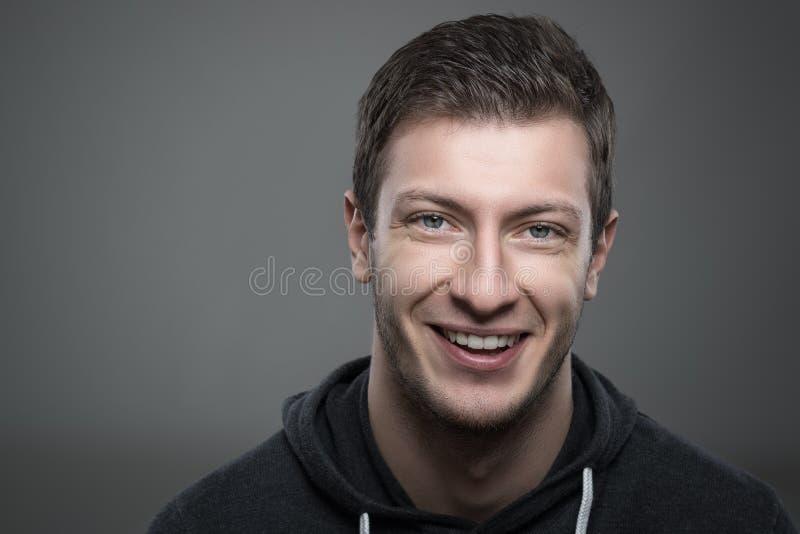 关闭微笑和看照相机的年轻不剃须的人喜怒无常的画象  免版税库存图片