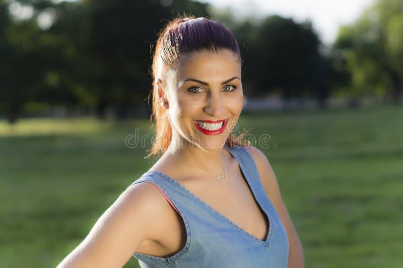 关闭微笑在公园的少妇画象 库存照片