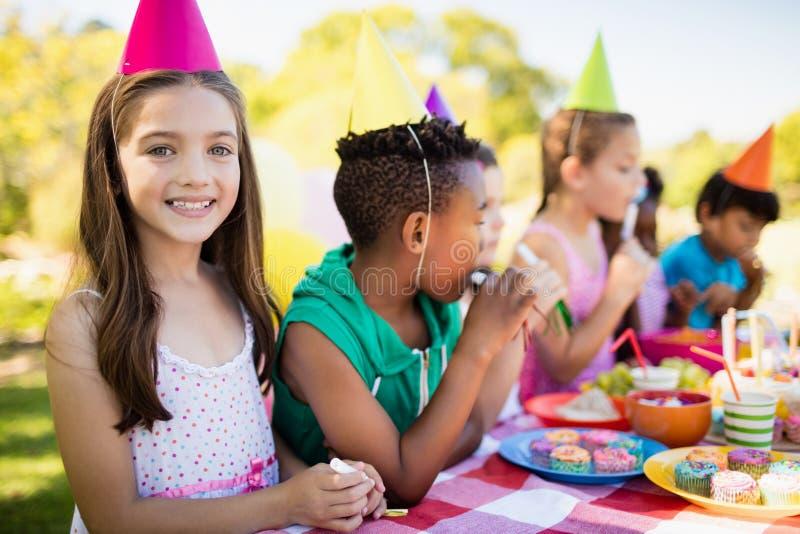 关闭微笑在其他孩子前面的逗人喜爱的女孩在生日聚会期间 免版税库存图片