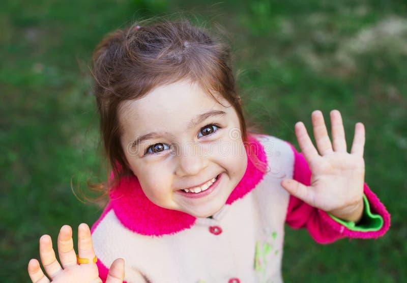 关闭微笑对照相机的逗人喜爱的愉快的小女孩画象  免版税库存图片