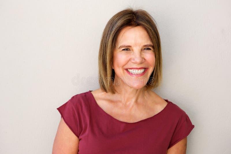 关闭微笑对白色墙壁的美丽的中年妇女 免版税库存图片