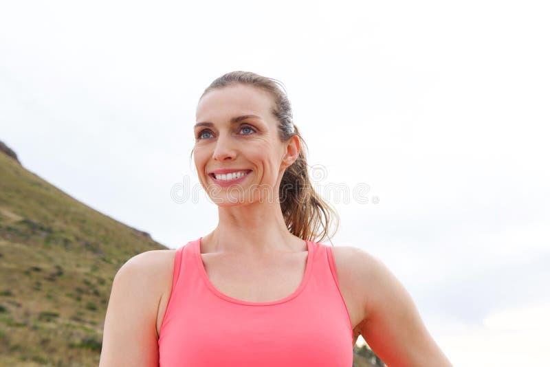 关闭微笑户外在行使前的妇女画象 免版税库存照片