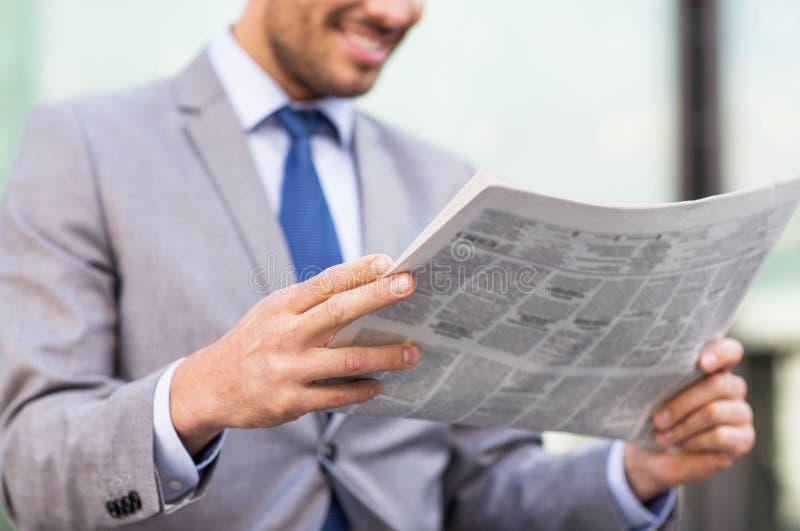 关闭微笑的商人读书报纸 免版税库存图片