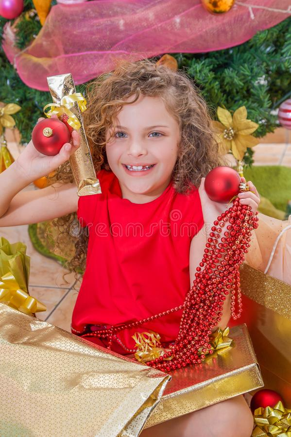 关闭微笑的女孩穿一件红色女衬衫和拿着圣诞节球的,装饰和礼物在她的手上,有a的 库存照片