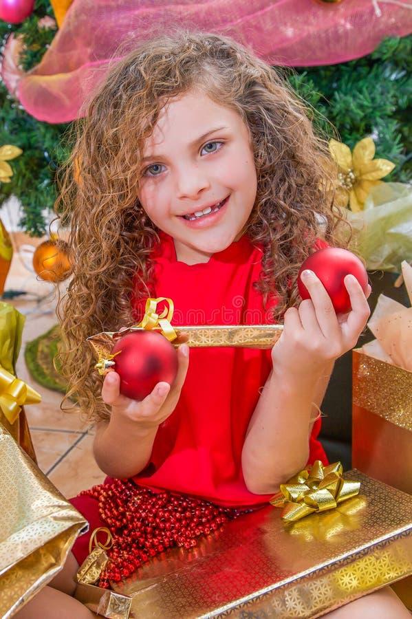 关闭微笑的女孩穿一件红色女衬衫和拿着圣诞节球的,装饰和礼物在她的手上,有a的 免版税库存图片