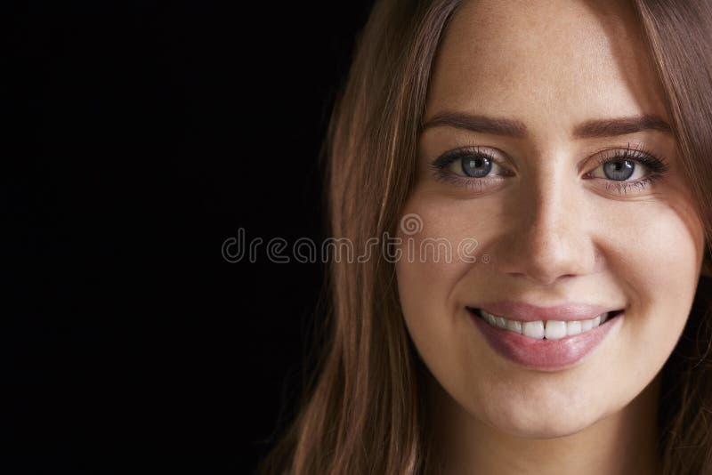关闭微笑的妇女首肩演播室画象  免版税库存图片