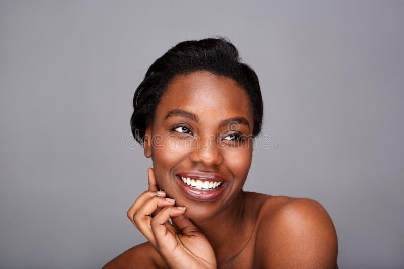 关闭微笑的黑人妇女用手面对和露出肩膀 图库摄影