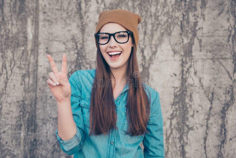 关闭快乐的嬉戏的女孩画象,打手势豌豆 免版税库存照片
