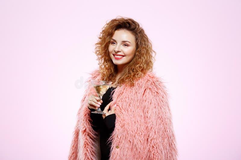 关闭快乐的微笑的美丽的深色的卷曲女孩画象拿着在白色的桃红色皮大衣的鸡尾酒杯 免版税库存照片