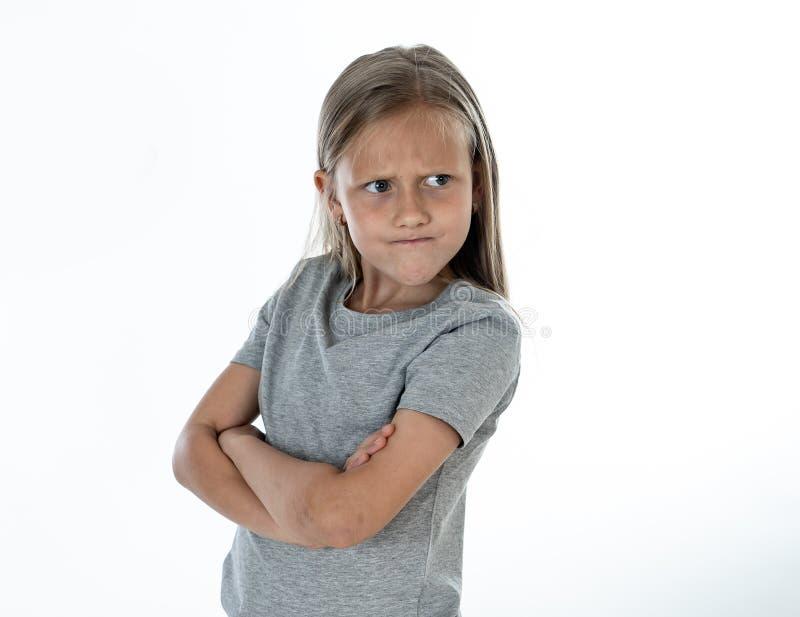 关闭恼怒和哀伤的矮小的白肤金发的女孩画象白色后面地面的 图库摄影
