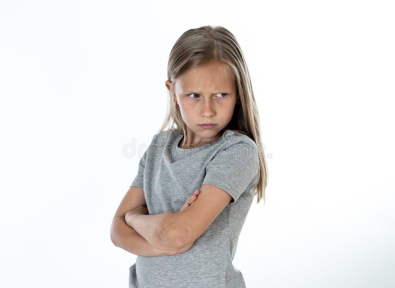 关闭恼怒和哀伤的矮小的白肤金发的女孩画象白色后面地面的 免版税库存照片