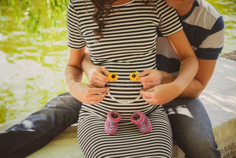关闭愉快的孕妇画象与拿着小童鞋的丈夫一起,拥抱在夏天公园 免版税库存图片