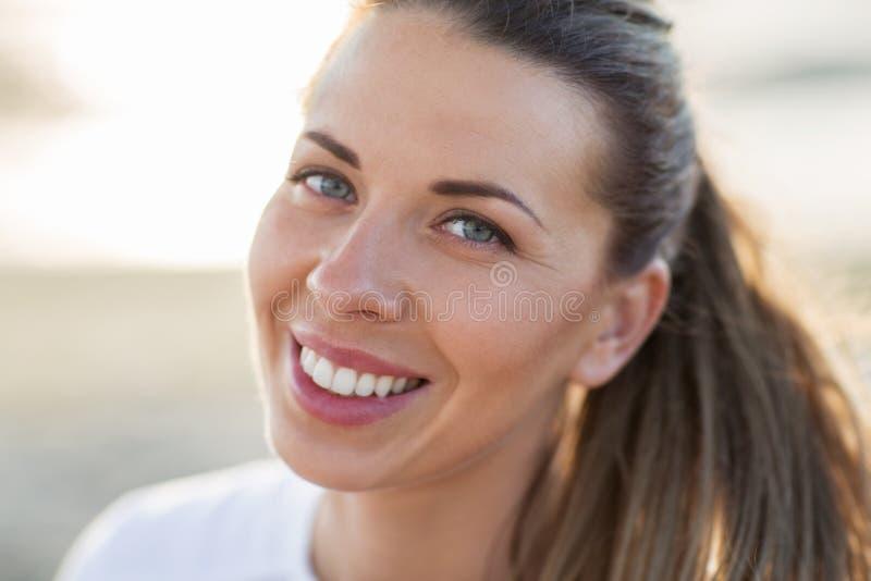 关闭愉快的微笑的少妇面孔 免版税图库摄影