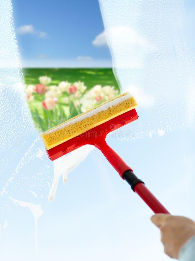 关闭手与海绵的清洁窗口 免版税库存图片