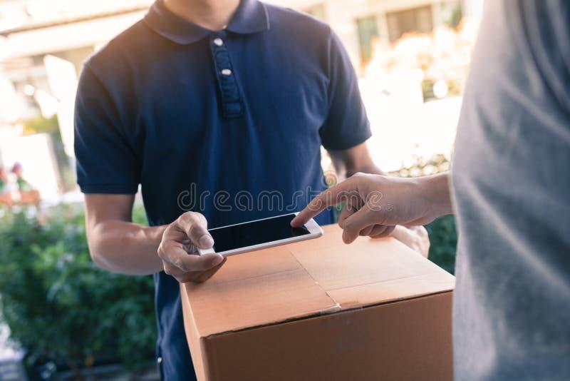 关闭手亚裔人使用按屏幕的智能手机为从传讯者的交付在家签字 库存照片