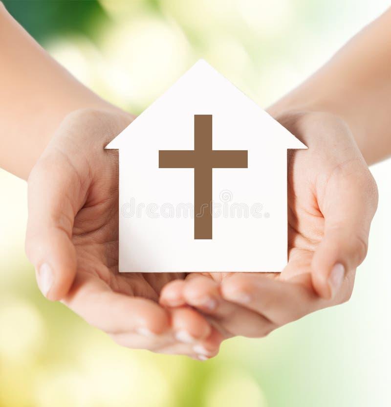 关闭手和纸房子有十字架的 免版税库存照片
