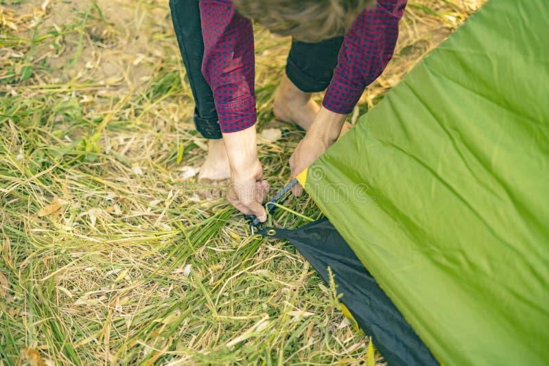 关闭手在自然森林阵营d的设定帐篷 免版税库存图片