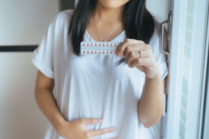 关闭手女性举行的避孕药,避孕的概念 库存照片