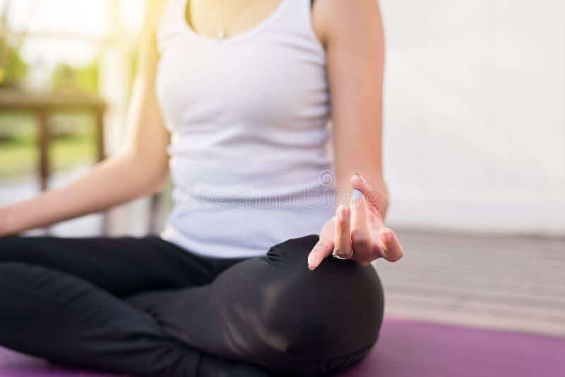 关闭手妇女实践瑜伽和凝思在莲花姿势 免版税库存图片