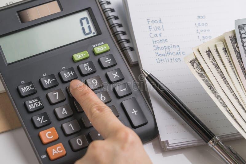 关闭手按在计算器的妇女按钮有预算、费用和费用名单的在小笔记薄,金钱 免版税库存图片