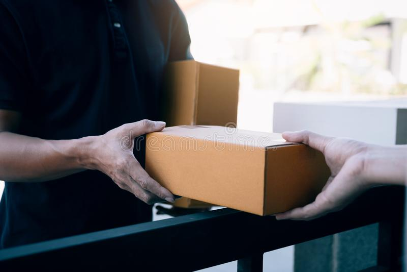 关闭手职员交付有里面小包的纸板箱到接收者的手的货物 库存照片