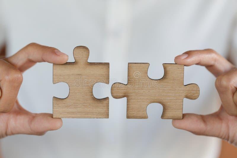 关闭手连接曲线锯的puzzleon,配合工作场所成功和战略概念的女商人 库存照片