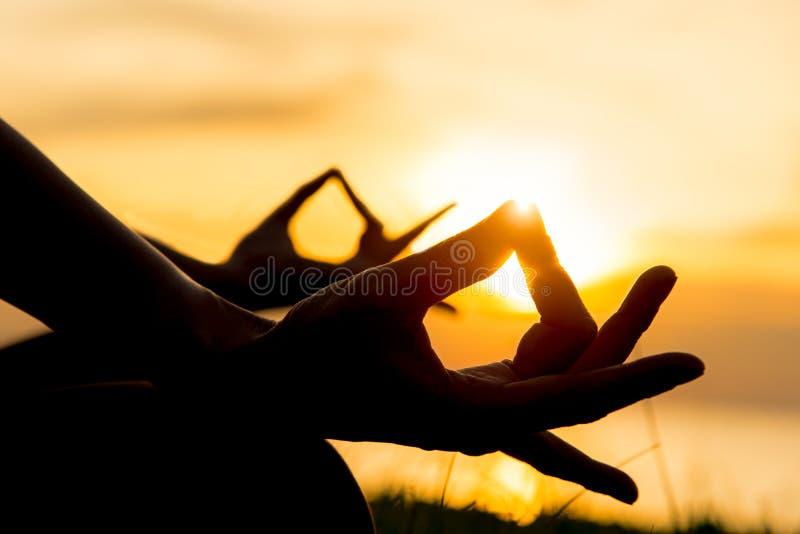 关闭手 妇女做室外的瑜伽 妇女健身生活方式的行使重要和凝思在海滩日落背景中 库存图片