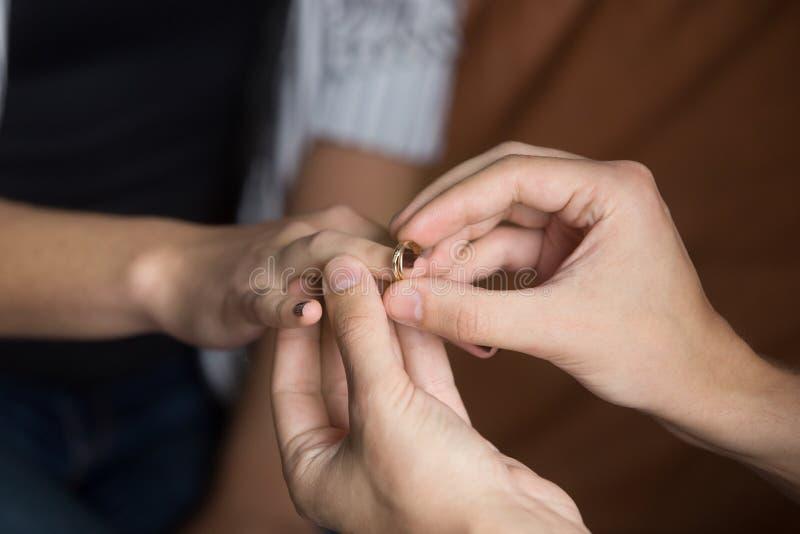 关闭把婚戒放的人在妇女手指上 库存图片
