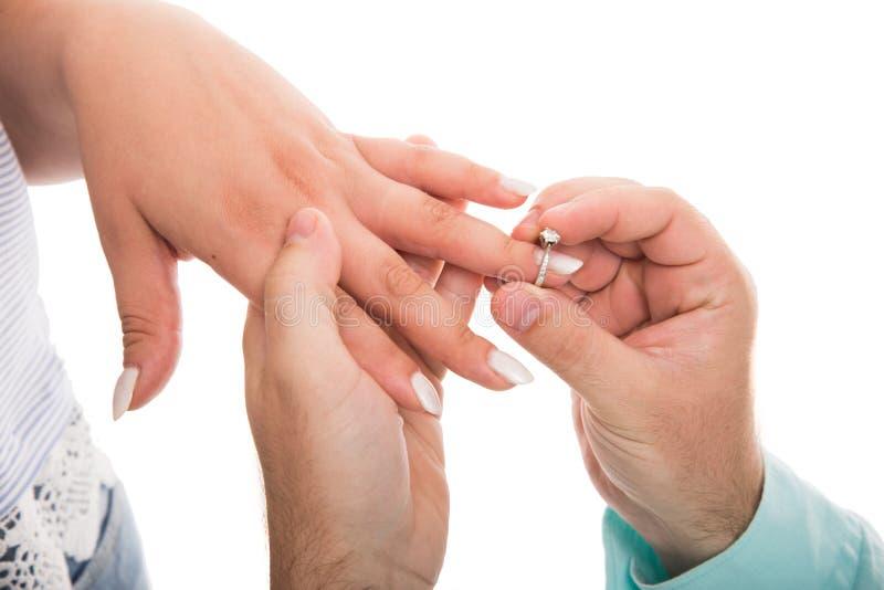 关闭把定婚戒指放的人在女朋友手指上 库存图片