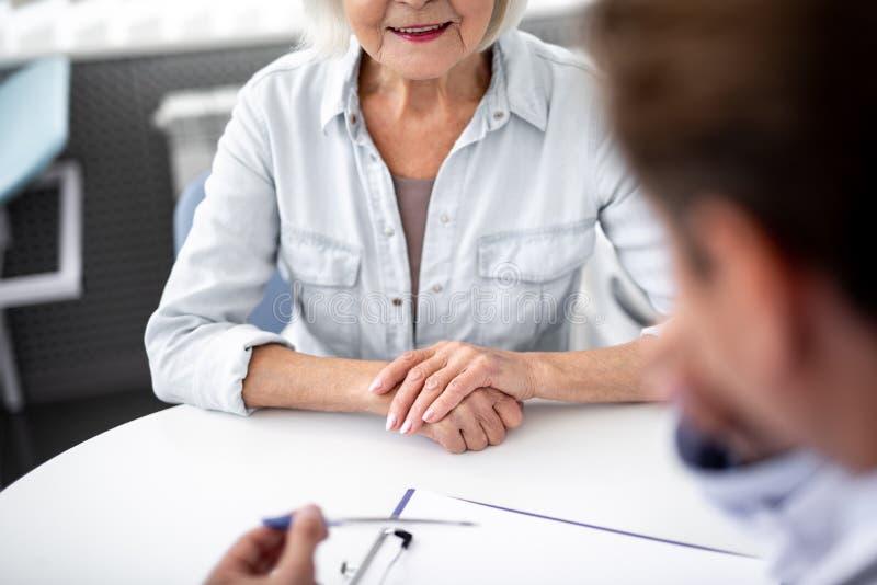 关闭把手放的年迈的妇女在桌上,当拜访实习者时 免版税库存照片