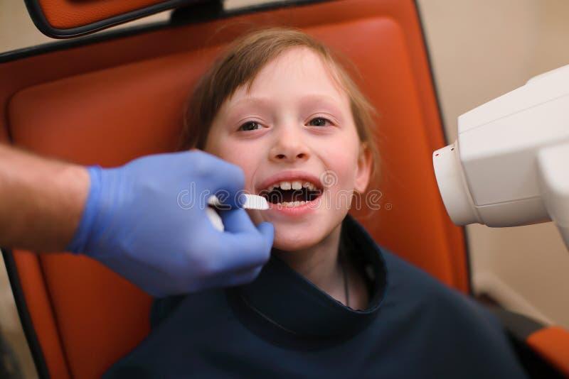 关闭投入口内的盾对儿童耐心嘴和辅助指挥的X光机的牙医在牙齿诊所 库存照片