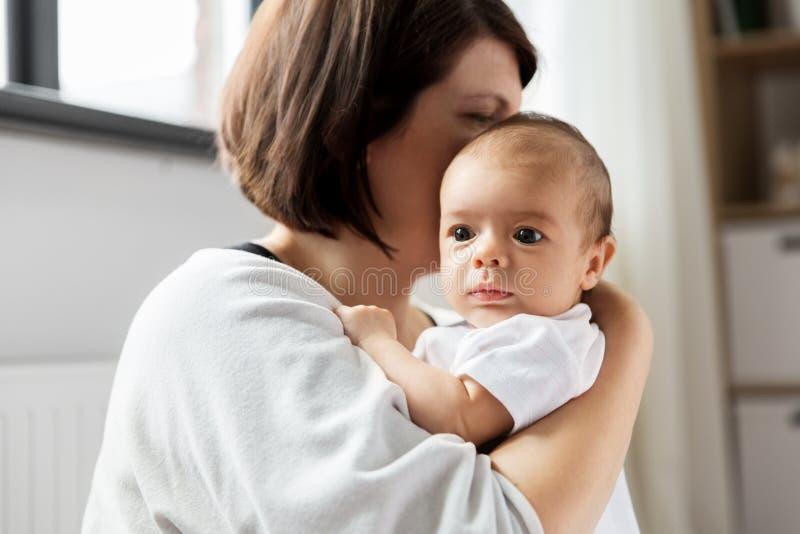 关闭抱着她的婴孩的母亲 免版税库存图片
