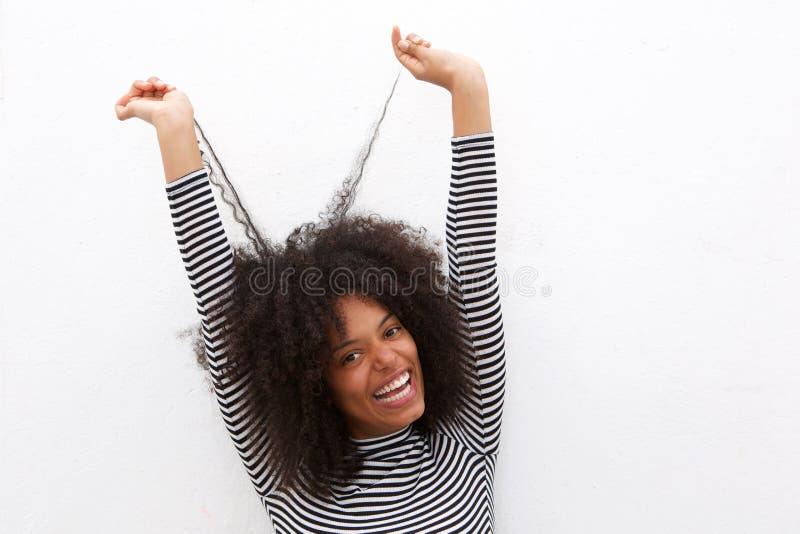 关闭拉扯卷发的美丽的愉快的黑人妇女 图库摄影
