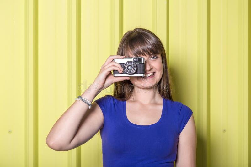 关闭拍与减速火箭的影片照相机的女孩画象照片在黄色背景 库存图片