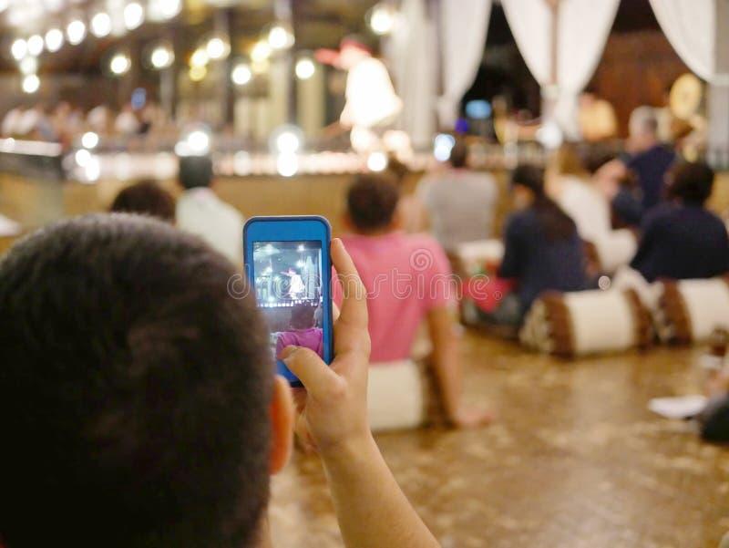 关闭拿他的电话的旅游` s手起拍美好的传统北泰国舞蹈照片  免版税库存照片