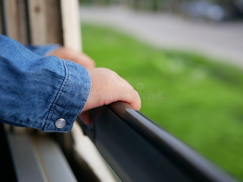 关闭拿着一个被打开的窗口的框架的在一列旅行的火车的小的婴孩` s手 免版税图库摄影