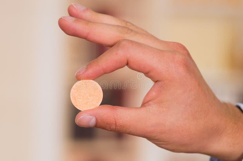 关闭拿着一种冒泡片剂在他的手上的一个人有被弄脏的背景 免版税图库摄影