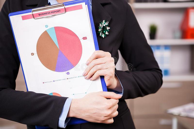 关闭拿着业务报告图的女实业家 免版税库存照片