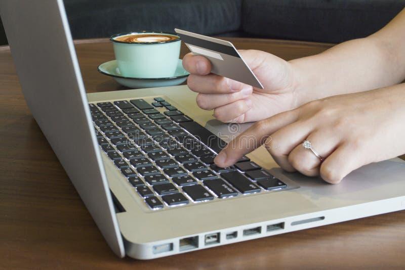 关闭拿着信用卡和使用笔记本c的妇女手 免版税库存照片