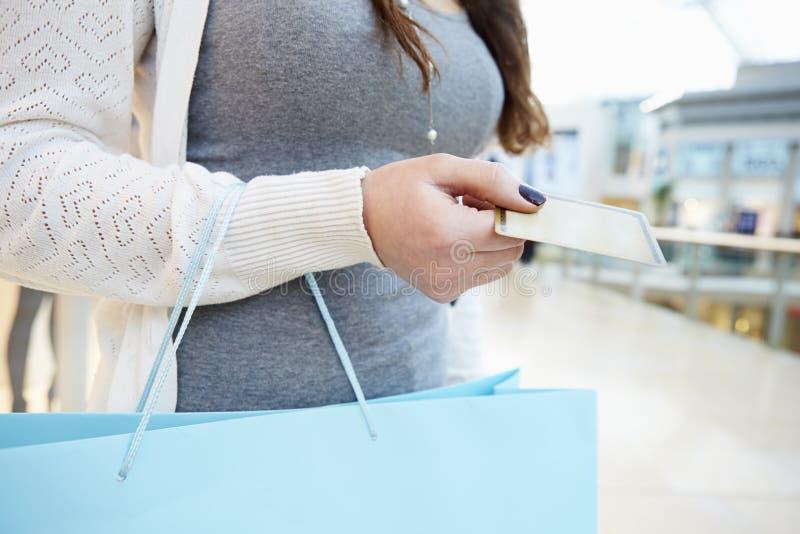 关闭拿着信用卡和袋子在购物中心的顾客 免版税库存照片