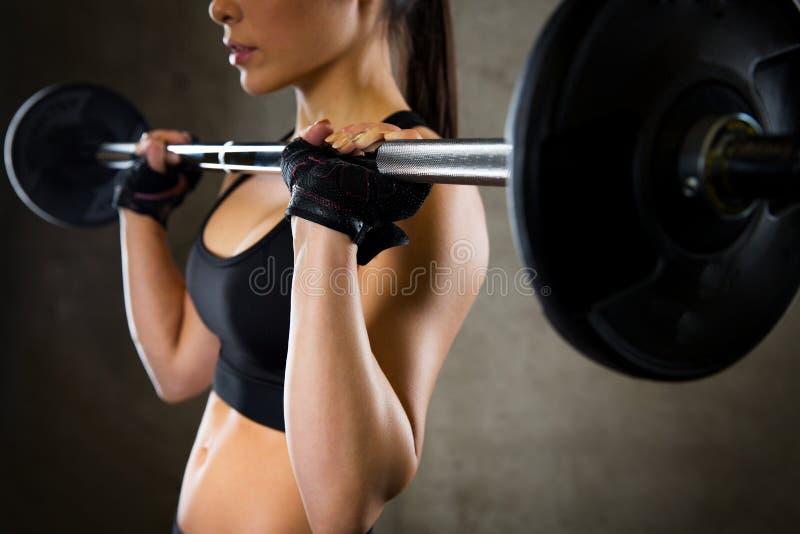 关闭拿着在健身房的妇女杠铃 库存图片