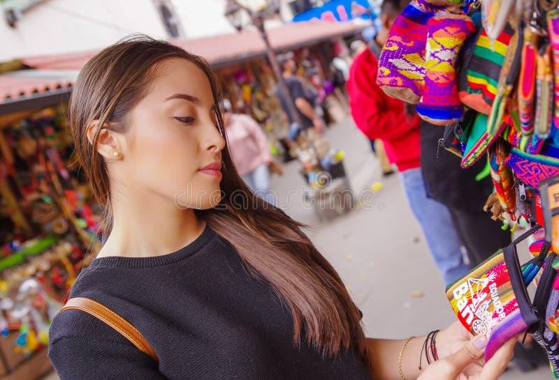 关闭拿着在她的手上印地安手工制造钱包的微笑的妇女在段落工艺的一家工艺商店在 库存图片