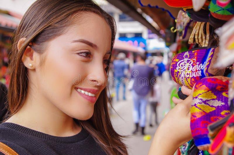 关闭拿着在她的手上印地安手工制造钱包的微笑的妇女在段落工艺的一家工艺商店在 免版税库存照片