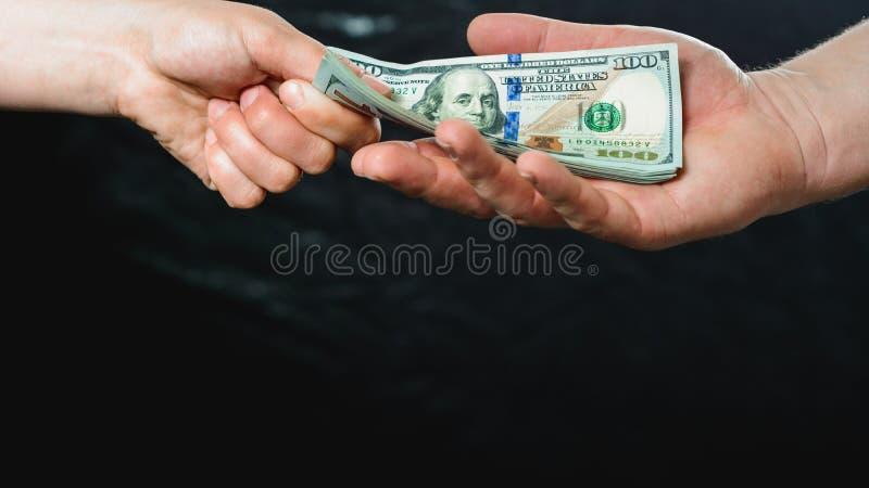 关闭拿着在黑背景的商人的手金钱 免版税库存图片